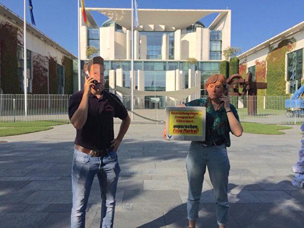 「為了被脅迫民族協會」成員帶著默克爾和習近平的面具,表演歐中對話活報劇。(大紀元)