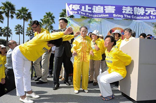 2013年10月20日,洛杉磯,集會上法輪功學員王春英(左)演示中共迫害的酷刑。(宋祥龍/大紀元)