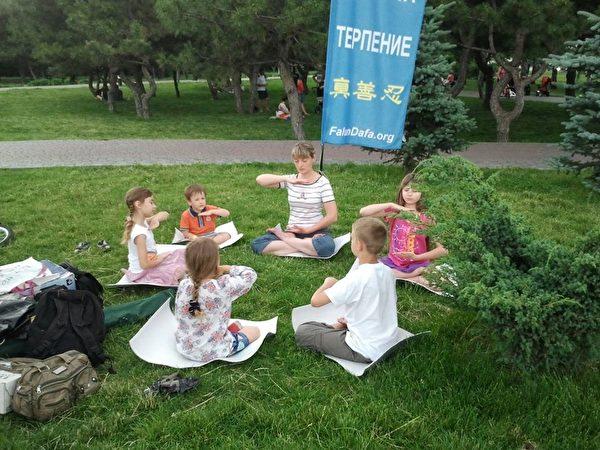 奧勒爾和幾位兒童在公園一起習煉法輪大法的第五套功法,她們的座姿就叫蓮花座。(Mishchenko Olga via Armina Nimenko提供)