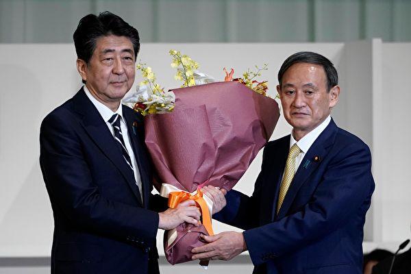 2020年9月14日,日本東京,即將卸任的首相安倍晉三從自民黨新總裁菅義偉(右)手中接過鮮花。(EUGENE HOSHIKO/POOL/AFP via Getty Images)