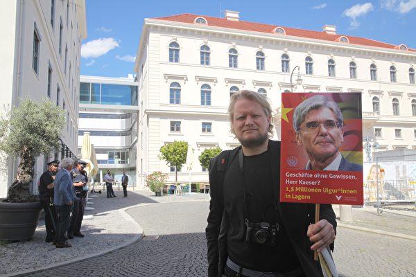 2020年7月27日,「為了被脅迫民族協會(GfbV)」德國項目負責人賽德勒(Hanno Schedler)手舉著西門子總裁凱颯頭像,在西門子總部前抗議。(黃芩/大紀元)