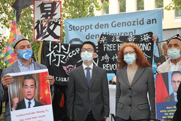 參加集會的德國聯邦議員、綠黨人權政策發言人鮑澤(Margarete Bause,Grune,右二)和羅冠聰(左二)、歐洲東突協會主席阿斯加.禪(Asgar Can,左一)站在一起。(黃芩/大紀元)