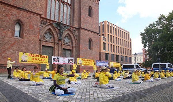 法輪功學員以煉功和打橫幅的形式,抗議中共21年來對法輪功的迫害。(黃芩/大紀元)