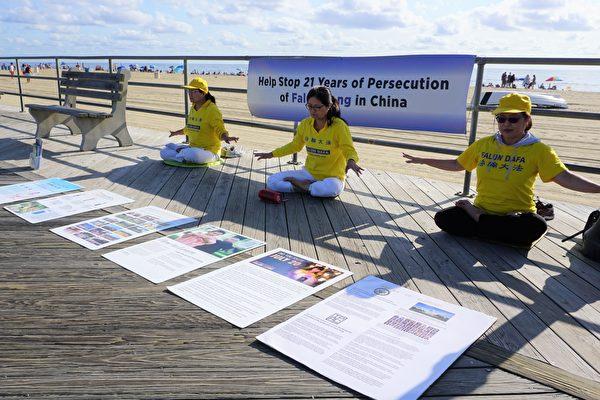 勞動節長周末,多名身著黃色T恤衫的法輪功學員來到阿斯伯里公園市的海灘。他們在木板路旁掛起橫幅,在地上擺放真相展板,伴隨著悠揚舒緩的煉功音樂,展示法輪功的五套功法。(鐘仁/大紀元)
