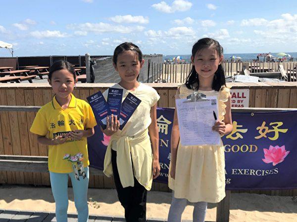 三位小學員也向遊客發真相傳單和徵簽。(鐘仁/大紀元)