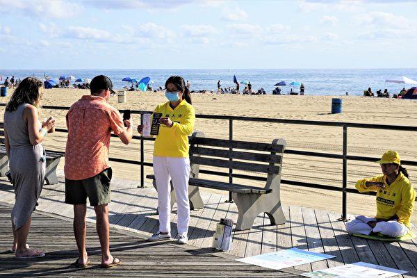 男遊客用手機拍下了學員握著的大法傳單。(鐘仁/大紀元)