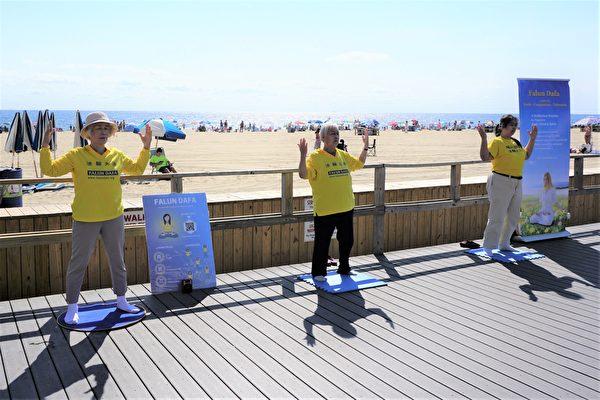 勞動節長周末,新澤西多名法輪功學員來到快樂點市的海灘。他們在木板路旁掛起橫幅,擺放展板,伴隨著悠揚舒緩的煉功音樂,展示法輪功的五套功法。(鐘仁/大紀元)