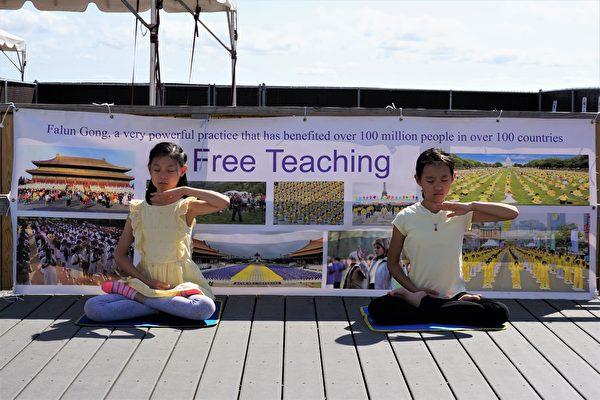 同來的還有三位小學員,她們煉功時平靜的表情和心態,也吸引了不少遊客的目光。(鐘仁/大紀元)