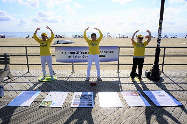 勞動節長周末,新澤西多名法輪功學員來到阿斯伯里公園市的海灘。他們在木板路旁掛起橫幅,在地上擺放真相展板,伴隨著悠揚舒緩的煉功音樂,展示法輪功的五套功法。(鐘仁/大紀元)