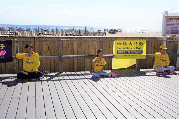 勞動節長周末,新澤西多名法輪功學員來到快樂點市的海灘。他們在木板路旁掛起橫幅,伴隨著悠揚舒緩的煉功音樂,展示法輪功的五套功法。(鐘仁/大紀元)