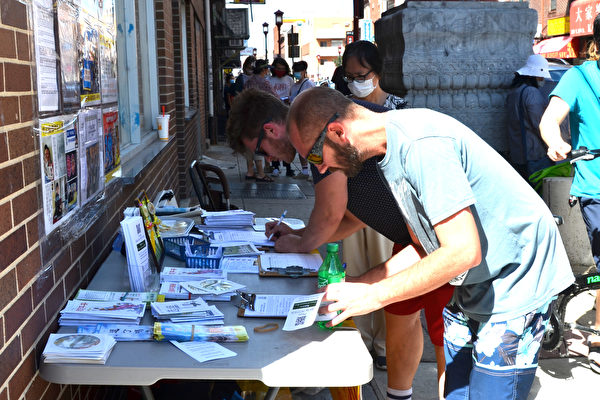 民眾在聲援全球打倒中共的請願書上簽了字。(良克霖/大紀元)