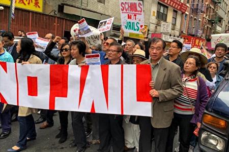 圖為2019年10月6日,許多華人團體舉行遊行,抗議市府在華埠建設40層的監獄。圖中(右一)手舉橫幅者為馬來西亞旅美聯誼會主席邦君雄。