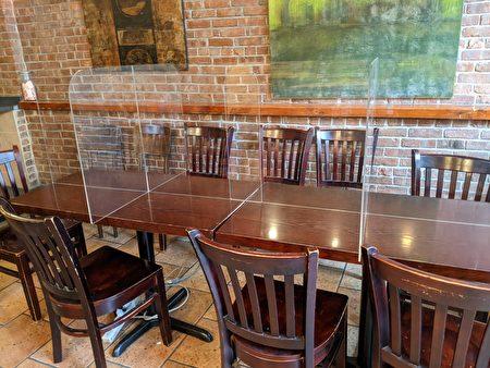 絲路茶館在餐桌設置透明實體隔板,為月底開放室內用餐做好防疫準備。