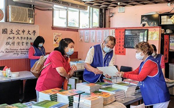 圖:國立空中大學加拿大專班9月舉辦開學典禮,圖為志工們在發放課本。(空大提供)