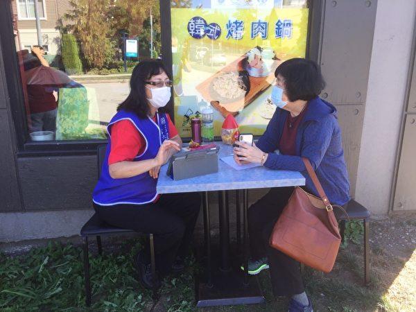 圖:楓情讀書會副會長楊張芝(左),熱情服務學妹。(空大提供)