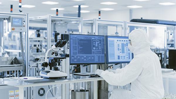 圖為:在實驗室中的科學家在保護衣服在個人電腦上做研究。現代化製造廠生產半導體及藥品。(Shutterstock)