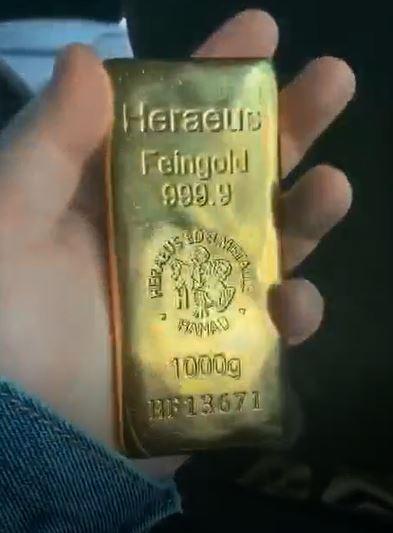 伊啟威倒賣黃金時,做了錄像。他在影片中手持一塊序列編號為HF13671的黃金金條。圖為伊啟威的影片截圖。(大紀元)