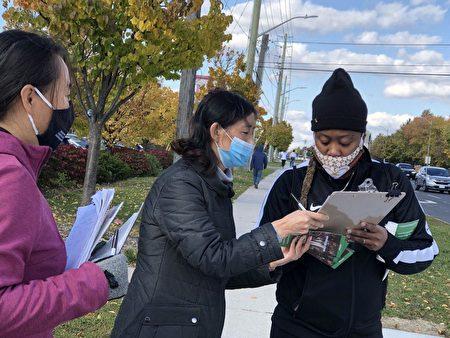 10月24日、25日,多倫多法輪功學員街頭徵簽呼籲終結中共,市民簽名支持。(潘學峰提供)