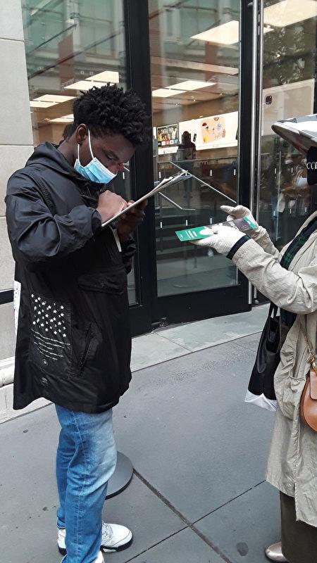 """Một người Mỹ gốc Phi đang ký tên vào bản kiến nghị """"Đả đảo Ác ma ĐCSTQ"""" ở Manhattan, New York. (Ảnh: Global Service Center for Quitting the Chinese Communist Party)"""