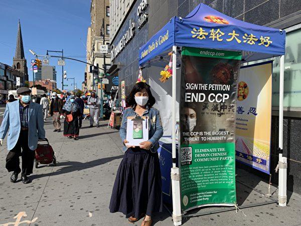"""Tình nguyện viên Dương Quý Vinh giới thiệu cho mọi người về hoạt động ký tên """"Đả đảo Ác ma ĐCSTQ"""" ở khu Main Street, Flushing, New York, Mỹ. (Lin Dan / Epoch Times)"""
