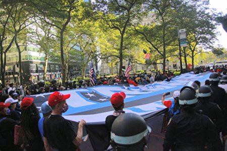 圖為川普總統支持者舉旗遊行曼哈頓百老匯街。