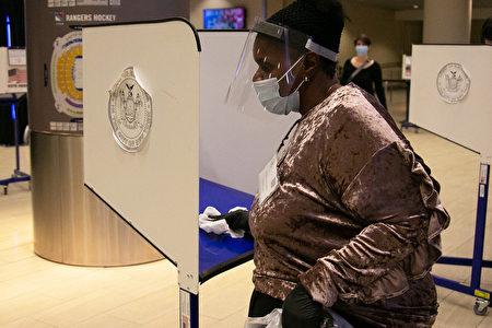 圖為2020年10月24日,投票站工作人員為投票亭清潔消毒。