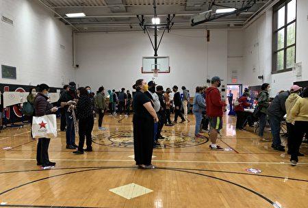 紐約華人社區法拉盛的投票站內,選民絡繹不絕,他們佩戴口罩,保持社交距離。