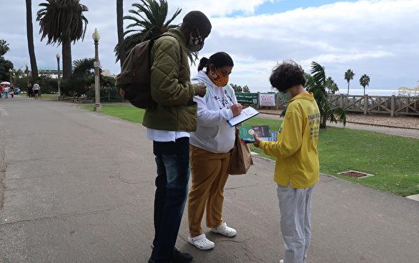 來自夏威夷的遊客伊莉莎白(Elizabeth)與布蘭登(Brandon)簽署了消滅中共的請願。(徐繡惠/大紀元)