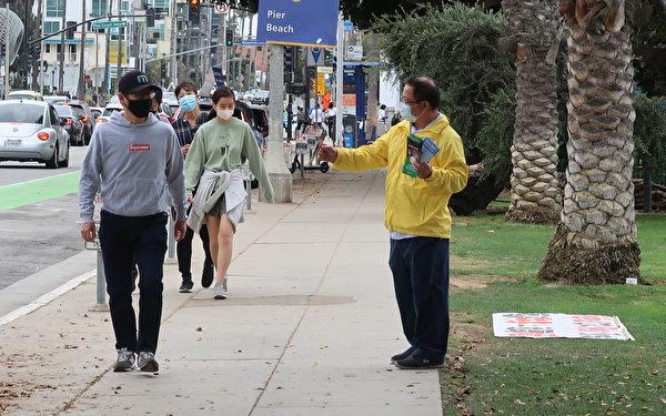 10月25日(周日),法輪功學員於聖莫妮卡海灘公園發送消滅中共的徵簽傳單。(徐繡惠/大紀元)