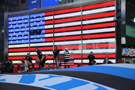 图为2020年10月13日,纽约市支持川普总统连任的民众,在时代广场进行集会,手举美国国旗。