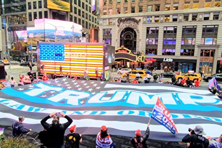 图为2020年10月13日,纽约市支持川普总统连任的民众,合力在时代广场前举起一面巨幅黑白相间,中间有蓝色条纹的美国国旗。