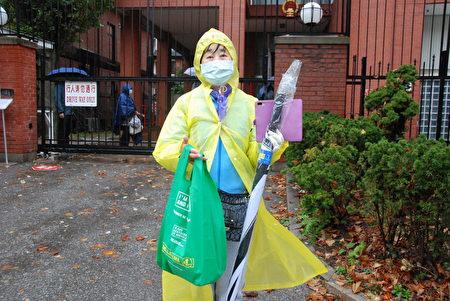 10月15日下午,一位白人男子拿著一把新買的傘,提著看一個膠袋來到三退義工前面,恭敬地雙手遞給義工潘女士,以表達支持。(伊鈴/大紀元)