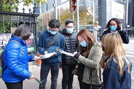 10月24日下午,一群香港留學生路過王后街和大學路口,看到橫幅後,都過來簽名。(伊鈴/大紀元)