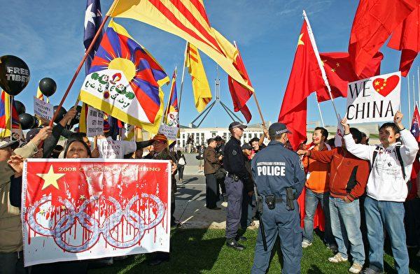 2008年4月24日,北京奧運會火炬傳遞坎培拉期間,警察在議會大廈外將西藏抗議者(左)和數千名支持者(右)分開。(TORSTEN BLACKWOOD/AFP via Getty Images)