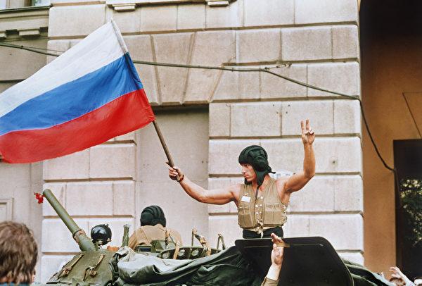 1991年8月21日,對戈巴卓夫總統發動軍事政變失敗後,裝甲部隊從莫斯科撤離,一名士兵在坦克頂部揮舞著俄羅斯國旗。(WILLY SLINGERLAND/AFP via Getty Images)