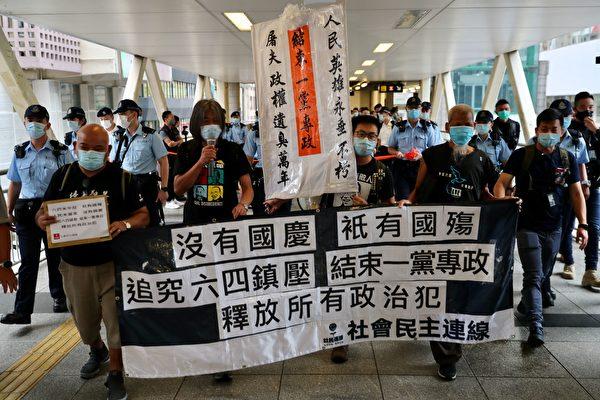 2020年10月1日,香港支聯會及社民連等團體到中聯辦外抗議,並要求釋放12名港人。警察緊跟其後。(MAY JAMES/AFP via Getty Images)