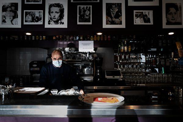 2020年10月9日,法國里昂的一家咖啡館的老闆在櫃檯後面工作。包括里昂、巴黎在內的四個法國城市正處於最高級別的中共病毒警報狀態,巴黎已關閉酒吧。(JEFF PACHOUD/AFP via Getty Images)