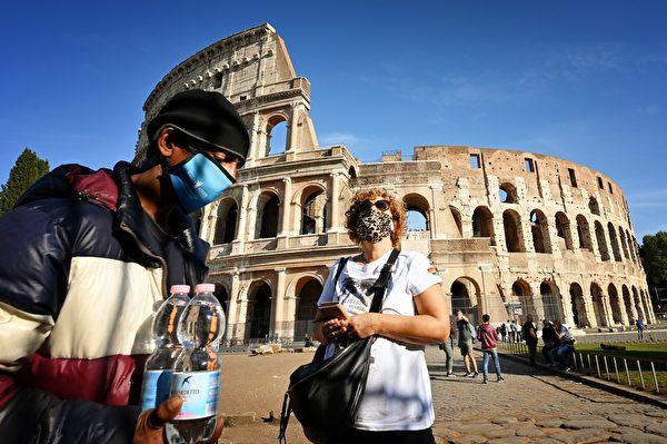 圖為2020年10月9日,羅馬競技場,一名戴口罩的街頭小販和一名婦女。意大利政府已強制要求在戶外必須戴口罩。(ALBERTO PIZZOLI/AFP via Getty Images)