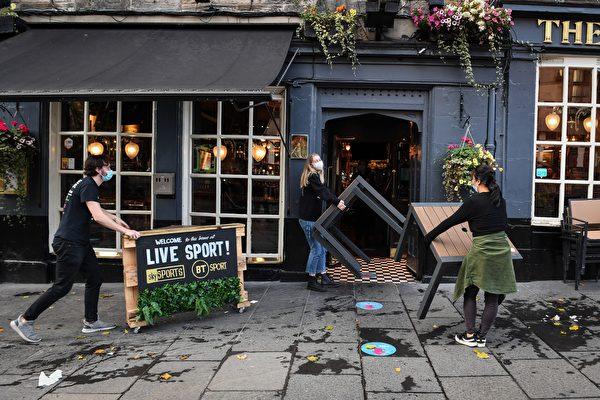 2020年10月9日,英國時間晚上6:00左右,愛丁堡一家酒吧的工作人員在收起桌子。蘇格蘭已下令關閉中部包括主要城市格拉斯哥和愛丁堡的酒吧,為期兩周。(ANDY BUCHANAN/AFP via Getty Images)