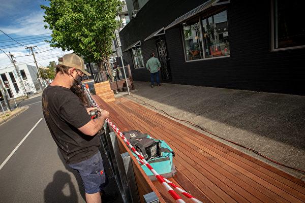 墨爾本一家具樂部的工人在室外安裝長凳