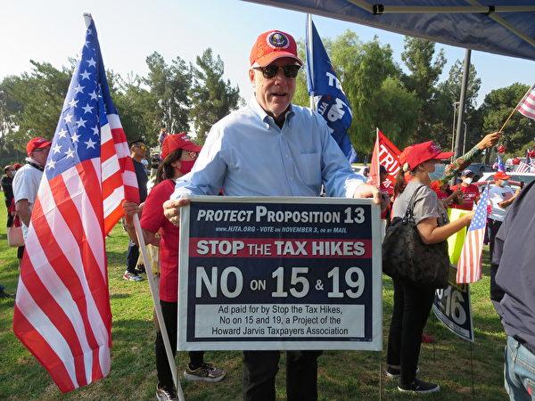 居民在集會上舉著反對15和19公投案的牌子。(李梅/大紀元)