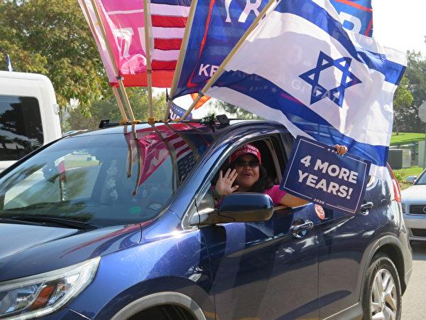 2020年10月,菲律賓裔美國人在洛杉磯核桃市舉行汽車拉力賽,駕車的女士拿出「再贏四年」的牌子。(李梅/大紀元)