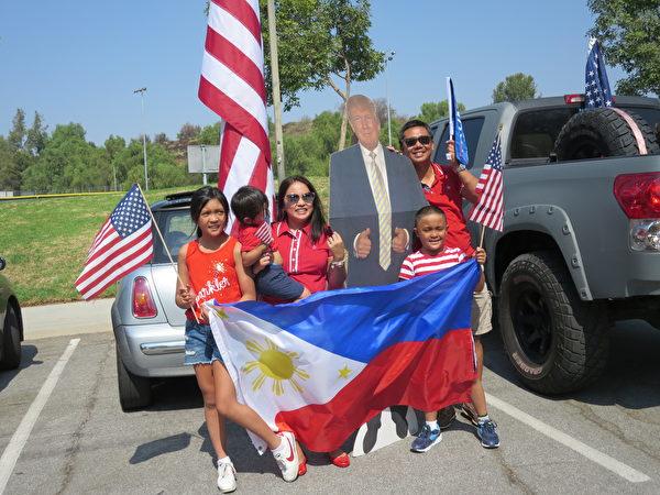 一家菲律賓裔美國人在洛杉磯核桃市參加集會和汽車拉力賽後和總統像合照。(李梅/大紀元)