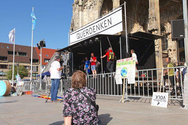 德國「橫向思維」於2020年9月20日在世界最高教堂——烏爾姆(Ulm)大教堂前舉辦活動,呼籲德國政府保障《基本法》。圖為集會主席台。(黃芩/大紀元)