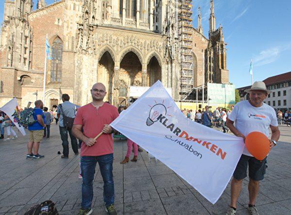 電子工程師托馬斯·施奈德(Thomas Schneider,左)手舉著「清晰思考」的旗子,參加了「橫向思維」在烏爾姆的活動。(黃芩/大紀元)