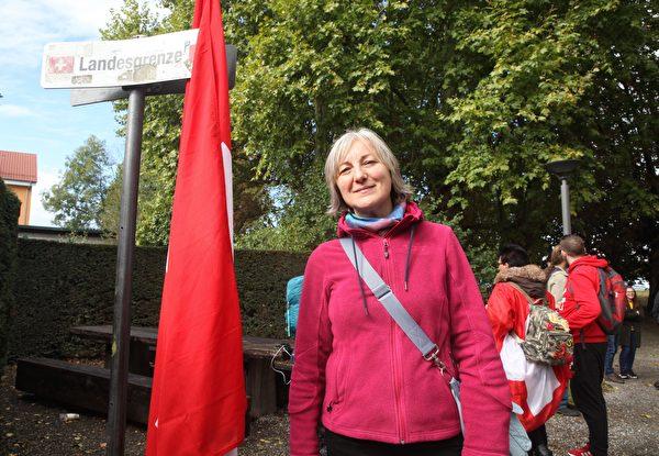 依娜.羅特女士(Ina Rothe)參加在博登湖的和平人鏈,她身旁是德國瑞士邊界標誌。(黃芩/大紀元)