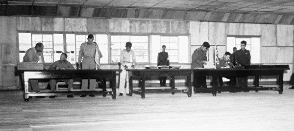 1953年7月27日,《北韓停戰協定》簽署現場,左側坐者為聯合國軍代表團首席代表、美國陸軍中將威廉·凱·海立勝,右側坐者為朝中代表,北韓軍隊大將南日。(公有領域)