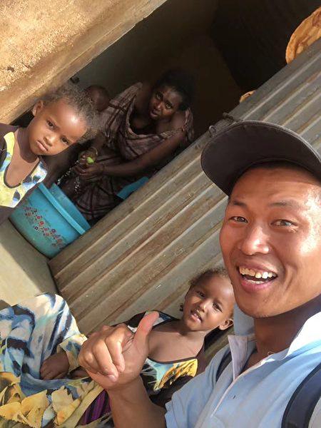 肯尼亞天氣炎熱高溫酷暑,小娃娃路上拽他給水喝。(受訪者提供)