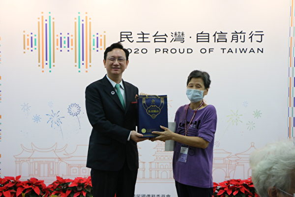 僑委會委員長童振源(左)2020年10月5日頒發紀念狀給首位報到僑胞陳羽莎。(李怡欣/大紀元)
