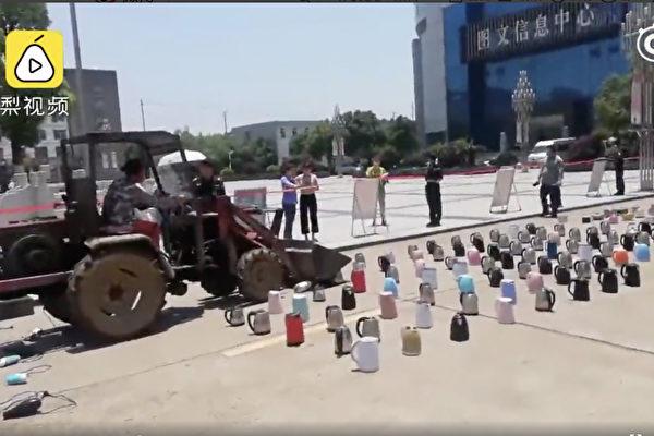 江西南昌一高校用推土機銷毀成片的電吹風、熱水壺等電器。(影片截圖)